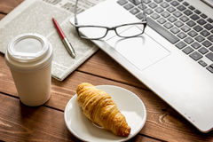 Business lunch with croissant and laptop on wooden desk Royalty Free Stock Image