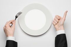 Business lunch and healthy food theme: man's hand in a black suit holding a white empty plate and shows finger gesture on an isola Stock Image