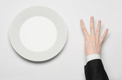 Business lunch and healthy food theme: man's hand in a black suit holding a white empty plate and shows finger gesture on an isola Royalty Free Stock Image