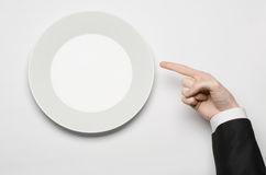 Business lunch and healthy food theme: man's hand in a black suit holding a white empty plate and shows finger gesture on an isola Royalty Free Stock Photo
