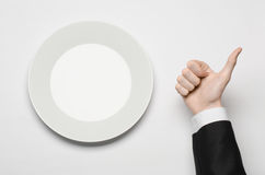 Business lunch and healthy food theme: man's hand in a black suit holding a white empty plate and shows finger gesture on an isola Royalty Free Stock Images