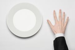 Business lunch and healthy food theme: man's hand in a black suit holding a white empty plate and shows finger gesture on an isola Stock Photography