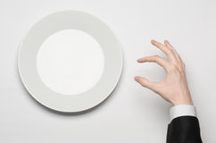 Business lunch and healthy food theme: man's hand in a black suit holding a white empty plate and shows finger gesture on an isola Stock Photo