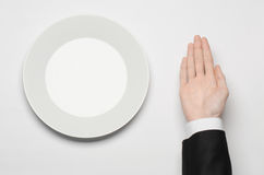 Business lunch and healthy food theme: man's hand in a black suit holding a white empty plate and shows finger gesture on an isola Royalty Free Stock Photos