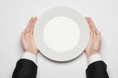 Business lunch and healthy food theme: man's hand in a black suit holding a white empty plate and shows finger gesture on an isola. Ted white background top view Royalty Free Stock Photos