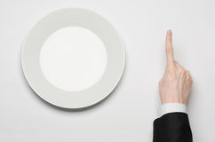 Business lunch and healthy food theme: man's hand in a black suit holding a white empty plate and shows finger gesture on an isola Stock Images