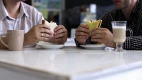 Business lunch. Two men eating sandwiches stock video