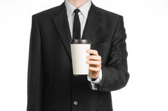 Business lunches coffee theme: businessman in a black suit holding a white blank paper cup of coffee with a brown plastic cap isol Stock Photography