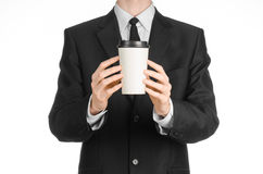 Business lunches coffee theme: businessman in a black suit holding a white blank paper cup of coffee with a brown plastic cap isol Royalty Free Stock Image