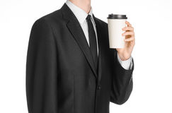 Business lunches coffee theme: businessman in a black suit holding a white blank paper cup of coffee with a brown plastic cap isol Royalty Free Stock Photography