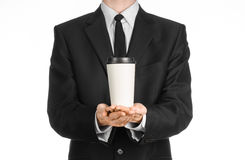 Business lunches coffee theme: businessman in a black suit holding a white blank paper cup of coffee with a brown plastic cap isol Royalty Free Stock Images