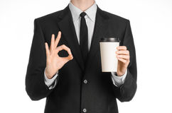 Business lunches coffee theme: businessman in a black suit holding a white blank paper cup of coffee with a brown plastic cap isol Royalty Free Stock Photos