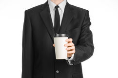 Business lunches coffee theme: businessman in a black suit holding a white blank paper cup of coffee with a brown plastic cap isol Stock Photos