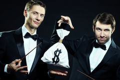Business magicians. Two magicians doing tricks with sack of money Stock Images