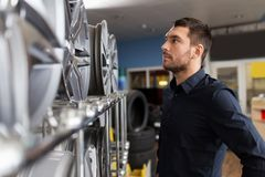 Male customer choosing wheel rims at car service. Business, maintenance and people concept - male customer choosing alloy wheel rims at car repair service or Royalty Free Stock Photo
