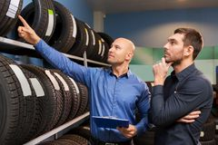 Customer and salesman at car service or auto store. Business, maintenance and people concept - male customer and salesman with clipboard showing wheel tires at royalty free stock photography