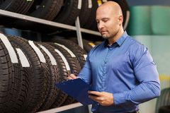 Auto business owner and wheel tires at car service. Business, maintenance and people concept - male manager with wheel tires and clipboard at car repair service Royalty Free Stock Photography