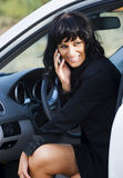 Business makes fun. A pretty young caucasian white business woman getting out of her nice car. She has a call on her smartphone while she is laughing and looking Stock Images