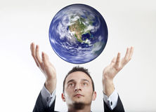Business makes the world go round. Businessman with spinning levitating earth between his hands stock photo