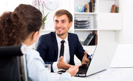 Business male assistant wearing formalwear using laptop. Successful business assistant wearing formalwear using laptop in company office Royalty Free Stock Photography