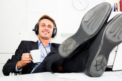 Business male employee relaxing with music in headphones. Positive business male employee relaxing with music in headphones in office Royalty Free Stock Photos