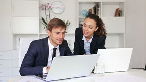 Business male and female  working using laptops. Two glad business male and female assistants wearing formalwear working using laptops in company office stock footage