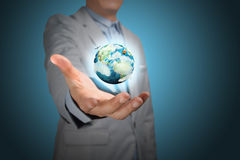 Business Male Hand hold earth globe. Business male hand hold eafth globe on blue background.  Elements of this image furnished by NASA Stock Photography