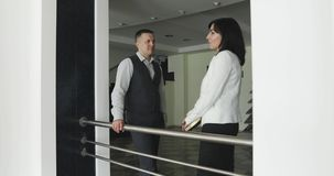 Business male and middle aged woman stand and talk in the hall of a modern office. stock video footage