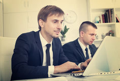 Business male sitting with coworkers in office royalty free stock photos