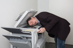 Business male in trouble with the copy machine at work. Male in trouble with the copy machine at work Royalty Free Stock Photography