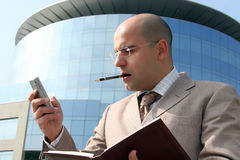 Business man. Holding cell phone up the business building Royalty Free Stock Photo