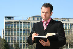 Business man. In the middle of writing up the business building Stock Photos