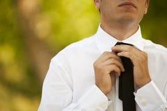 Business man. Portrait of a young business man arrange he's tie Stock Images