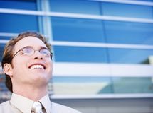 Business man. With glasses smiles in front of a business building Royalty Free Stock Images