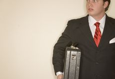 Business man 4. Business man in black suit, white shirt, and red tie holding briefcase looking off Stock Photo