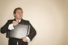 Business man 5. Business man in black suit, white shirt, and red tie holding briefcase making an expression Royalty Free Stock Images