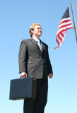 Business Man. Stands with his briefcase in front of the American Flag Royalty Free Stock Photo