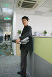 Business man. Asian Business man in black with file folders in hand Royalty Free Stock Image