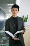 Business man. Asian Business man in black with a file folder in hand Royalty Free Stock Photo