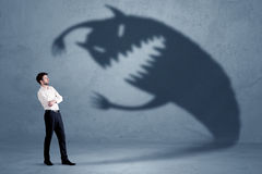 Business man afraid of his own shadow monster concept Royalty Free Stock Image