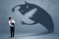 Business man afraid of his own shadow monster concept. On grungy background royalty free stock images