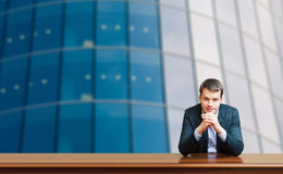 Business man against office windows Stock Photos