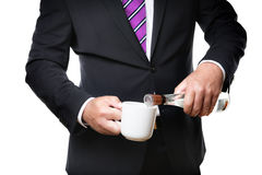 Business man with alcohol. Business man in dark suite with a coffee cup and a bottle with alcohol Stock Images