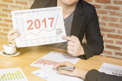 Business man analyze financial report graph year 2017 trend forecasting planning in cafe coffee shop Royalty Free Stock Photos