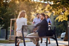 Free Business Man And Woman Sitting At Bench At Park And Talking Stock Photos - 182228133