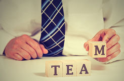 Business man arranging cubes reading Team on table. Power of cooperation partnership concept Stock Photography