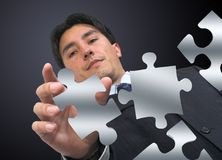 Business man arranging puzzle Stock Photos