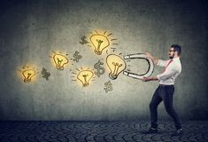 Business man attracts bright ideas light bulbs with a magnet stock photo