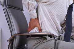 Business man with back pain sitting in an office chair. Pain relief concept Royalty Free Stock Photography