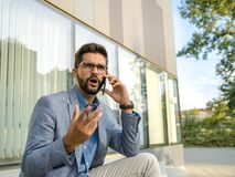 Business man in bad conversation on smartphone royalty free stock photography